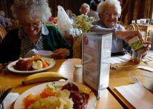 two older white women with grey and white hair sitting next to each other at restaurant eating dinner smiling
